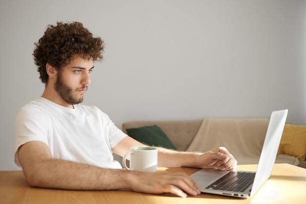 Openhartig schot van knappe zelfverzekerde jonge vrijgezel met dikke baard die thuis ontspannen met behulp van snelle draadloze internetverbinding op draagbare computer, websites browsen en koffie drinken na het werk