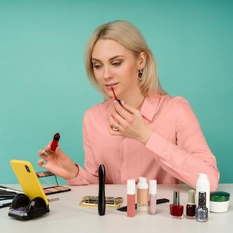 Openhartig schot van leuke jonge kaukasische vrouwenblogger die schoonheidsproducten voorstelt en uitzendt