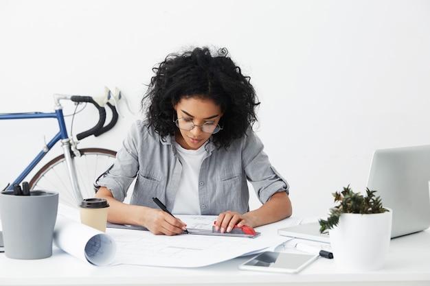 Openhartig schot van professionele bekwame afro-amerikaanse vrouwelijke architect met liniaal en pen