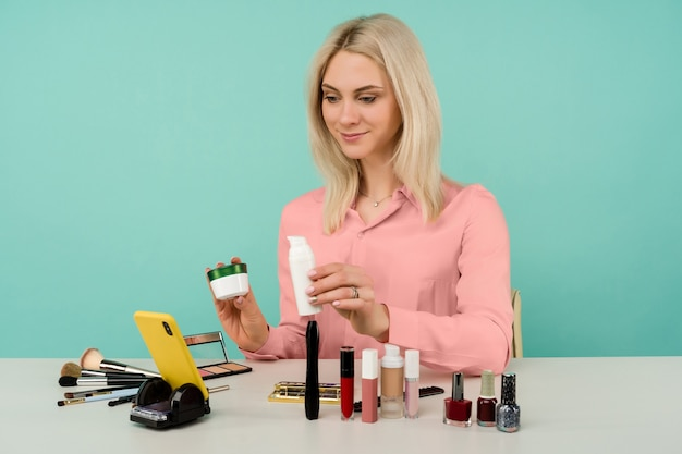 Openhartig schot van schattige jonge blanke vrouw blogger die schoonheidsproducten presenteert en live video uitzendt naar sociaal netwerk, waarbij anti-verouderingscrème wordt getoond tijdens het opnemen van dagelijkse make-uptutorial