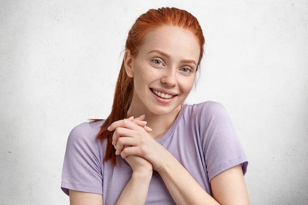 Openhartig schot van tevreden tevreden vrouwelijke student, verheugt zich over haar succes tijdens het studeren, lacht zachtjes naar de camera, heeft rood haar vastgebonden in paardenstaart, gekleed in casual paars t-shirt