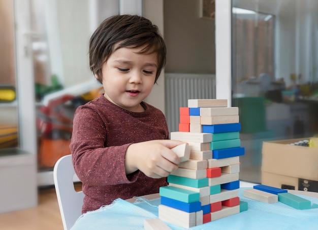 Openhartig schot van vrolijke kleine jongen speelt kleurrijke houten blokken in de speelkamer, portret van kind stapelen houten blokken thuis, educatief speelgoed voor kleuterschool en kleuterschool.