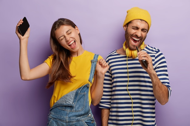 Openhartig shot van dolgelukkig energiek vriendje en vriendin luisteren muziek via mobiele telefoon, dansen en zingen luid, uiten positieve emoties, staan naast elkaar, heffen armen op en bewegen actief