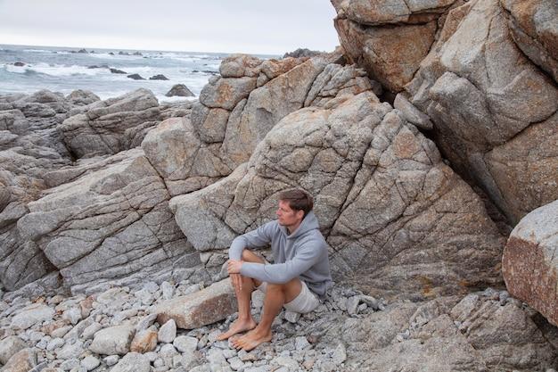 Openhartige authentieke duizendjarige man zittend op rotsachtige kust begroet zonsopgang