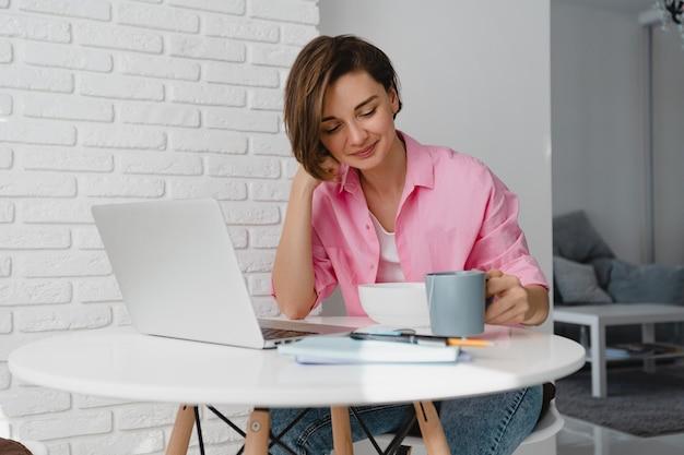 Openhartige lachende vrouw in roze shirt thuis ontbijten aan tafel online werken op laptop vanuit huis, granen eten
