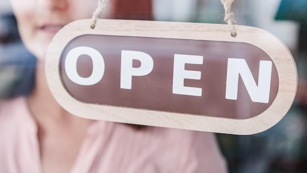 Opening van kleine bedrijven. het bord van dichtbij naar open draaien. onherkenbaar persoon