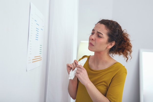 Openingstijden. zieke patiënte die bezorgd kijkt terwijl ze de spreekuren van doktoren bestudeert en zich afvraagt wanneer ze kan worden onderzocht