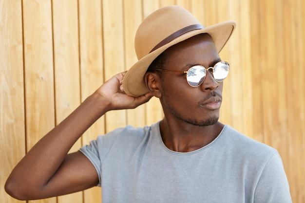 Openlucht de zomerportret van ernstige en zekere jonge zwarte student die buiten ontspannen, zijn modieuze hoed aanpassen, nadenkende blik hebben