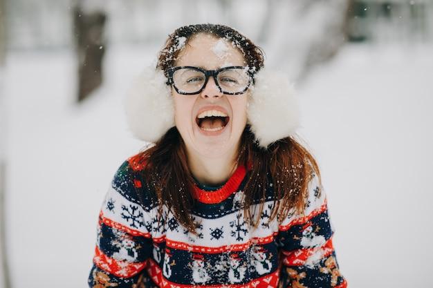 Openlucht dicht omhoog de winterportret van jong mooi meisje die oormoffen, sweater het stellen in sneeuwpark dragen. en vrouw die kijkt glimlacht