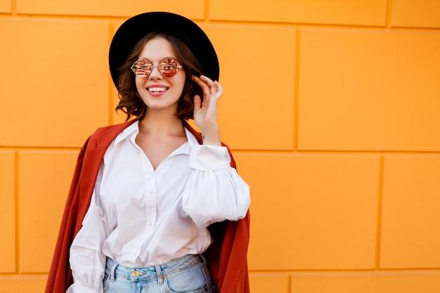 Openlucht dicht omhooggaand portret van het zalige donkerbruine kortharige vrouwelijke stellen over gele muur. trendy hoed, roze bril, witte blouse en jeans.