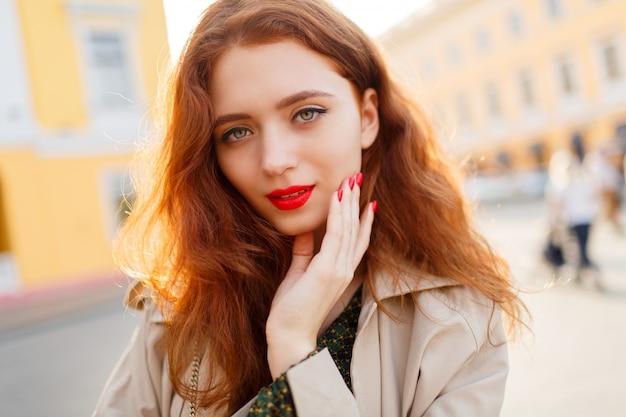 Openlucht dicht omhooggaand portret van mooie gembervrouw met golvende haren in beige laag. rode lippen en nagels.
