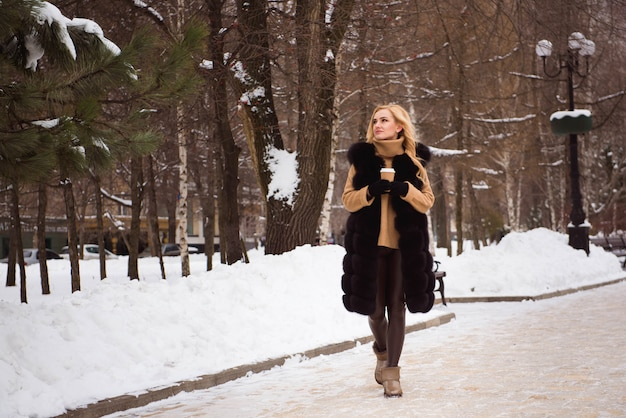 Openlucht dichte omhooggaande foto van jong mooi gelukkig glimlachend meisje die op straat in de winter lopen