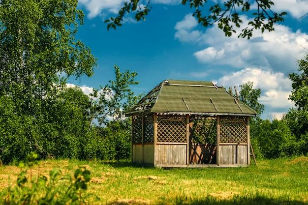 Openlucht houten gazebo met rozen en de achtergrond van het de zomerlandschap