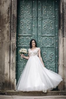 Openlucht portret van mooie jonge bruid in luxe witte jurk over oude deur