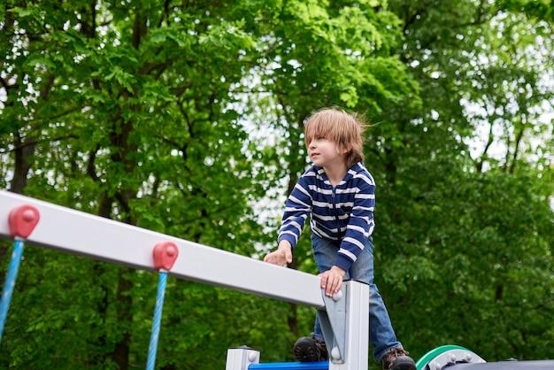 Openlucht portret van schattige peuter jongen klimmen op de speelplaats