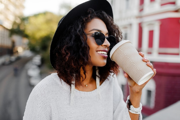 Openlucht positief beeld van het glimlachen van mooie zwarte in witte sweater en zwarte hoed die van koffie genieten om te gaan. stedelijke achtergrond.