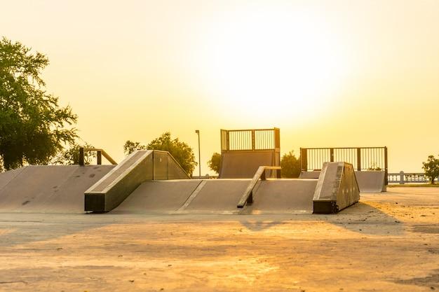 Openlucht skatepark met diverse hellingen op zonsondergangtijd