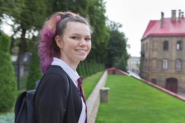 Openlucht tienerstudente met rugzak in eenvormige school