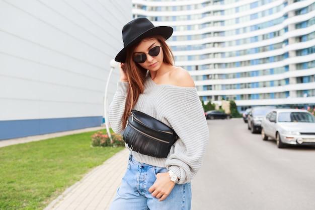 Openluchtbeeld van blij meisje in zwarte wollen hoed en grijze dalingssweater die en van gang in moderne stedelijke stad springen genieten.