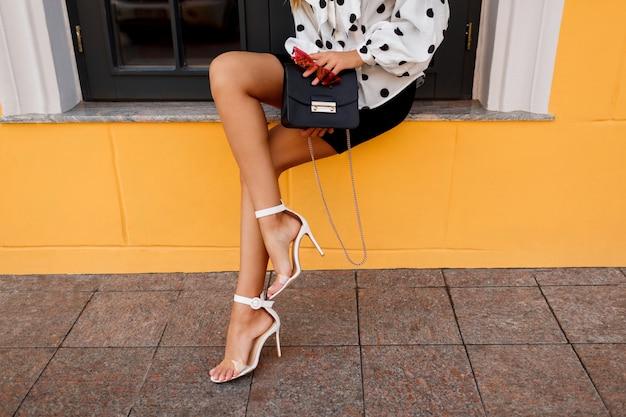 Openluchtbeeld van schitterende vrouw met benen in modieuze de lentekleren met het kleine zak stellen op de straat op geel.