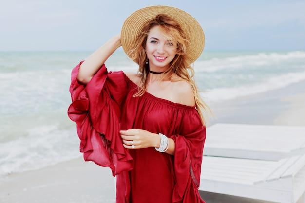 Openluchtlevensstijlportret van vrij witte gembervrouw in het modieuze kleding stellen op het strand dichtbij oceaan. blu hemel. winderig weer.