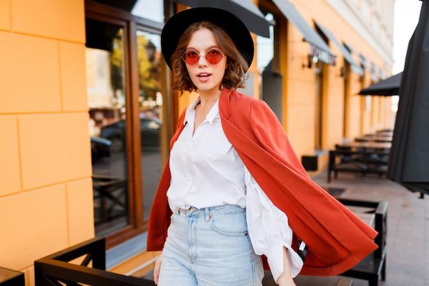 Openluchtmanierbeeld van jonge elegante vrouw die in oranje jasje en witte blouse in zonnige stad tijdens weekends lopen.