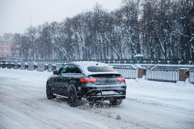 Openluchtmening van snelle autoritten op sneeuwweg op brug, tijdens koude de winterdag. sneeuwval in de stad