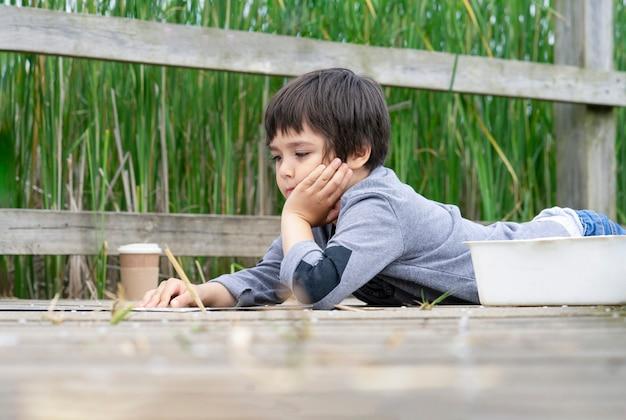 Openluchtportret die van gelukkige jongen op houten brug liggen die één of ander ding op papier lezen