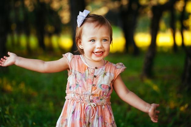 Openluchtportret van aanbiddelijk glimlachend meisje in de zomerdag