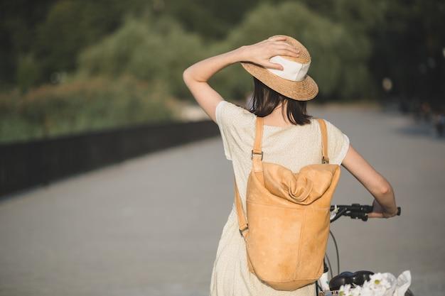 Openluchtportret van aantrekkelijk jong brunette in een hoed op een fiets.