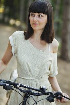 Openluchtportret van aantrekkelijk jong brunette op een fiets.