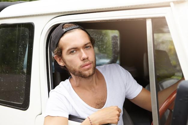 Openluchtportret van aantrekkelijke jonge hipster die met modieuze baard met zekere en trotse glimlach kijken terwijl het zitten in zijn wit safarivoertuig