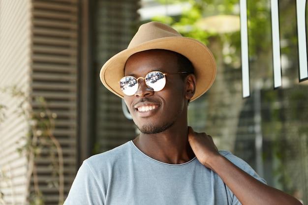Openluchtportret van aantrekkelijke modieuze donkerhuidige mens die spiegelglazen tinten dragen en hoed ontspannend op de zomerdag bij stedelijk restaurant, verbergend van brandende zonnestralen in schaduw door het venster