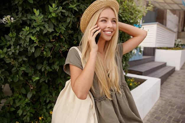 Openluchtportret van charmante blonde vrouw die haar hoed vasthoudt, casual linnen kleding draagt, een telefoontje geeft, in een goede bui is en breed lacht