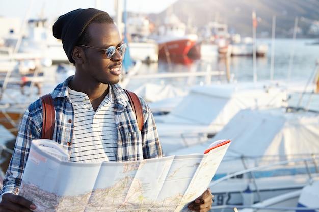 Openluchtportret van de afrikaanse mens die gelukkig vóór reis kijkt, wachtend op zijn vrienden in haven, houdend kaartkaart, opgewekt en blij voelt, anticiperend op avonturen, plaatsen en goede ervaring
