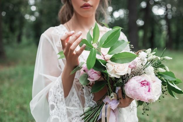 Openluchtportret van de bruid in een witte kanten peignoir houdt in haar handen een huwelijksboeket met rozen