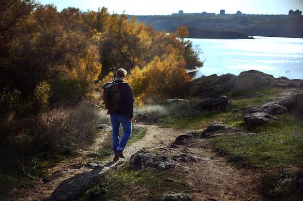Openluchtportret van de mens met rugzak die alleen reizen en onderweg berg lopen. prachtige natuur in de herfst