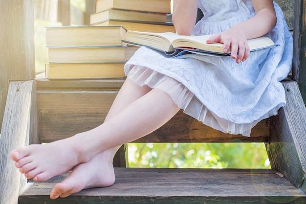 Openluchtportret van een aanbiddelijk jong meisje dat een boek in de tuin leest.