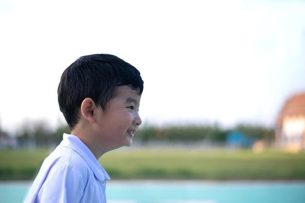 Openluchtportret van een gelukkig aziatisch studentenjong geitje