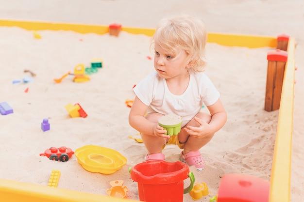 Openluchtportret van een gelukkig wit jong meisje dat in zandbak op een kinderspeelplaats speelt