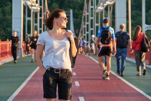 Openluchtportret van een gelukkige glimlachende rijpe vrouw die in zonnebril op de brug lopen