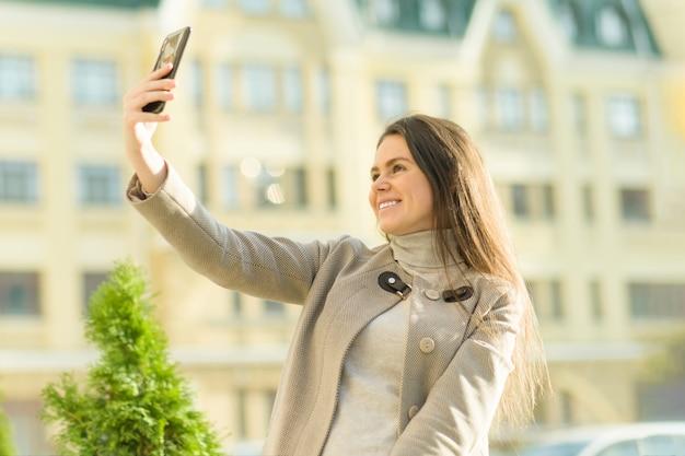 Openluchtportret van een glimlachende gelukkige jonge vrouw met smartphone