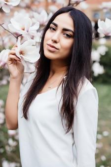 Openluchtportret van een jonge mooie vrouw dichtbij magnoliaboom met bloemen.