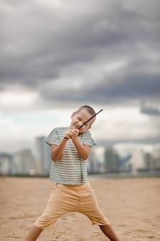 Openluchtportret van een kleine leuke jongen met stok