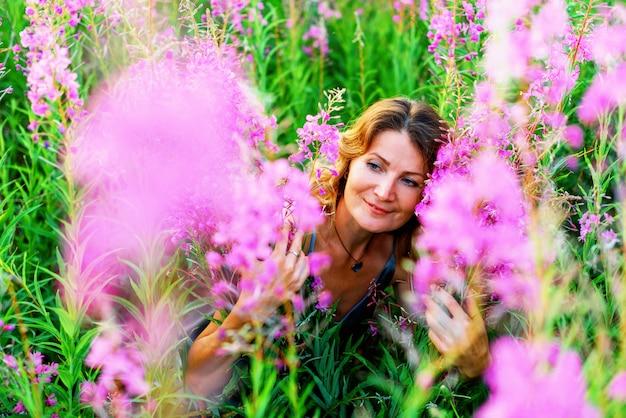 Openluchtportret van een mooie blonde vrouw van middelbare leeftijd in een gebied met bloemen
