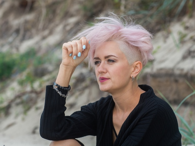 Openluchtportret van een mooie sexy jonge vrouw met roze haar en geschoren tempels die hipster meisje roken