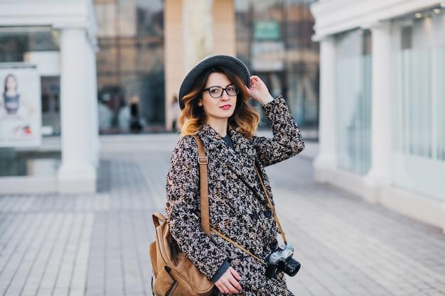 Openluchtportret van elegante jonge dame met bruine rugzak die jas en hoed draagt. aantrekkelijke vrouw met krullend haar die plezier hebben.