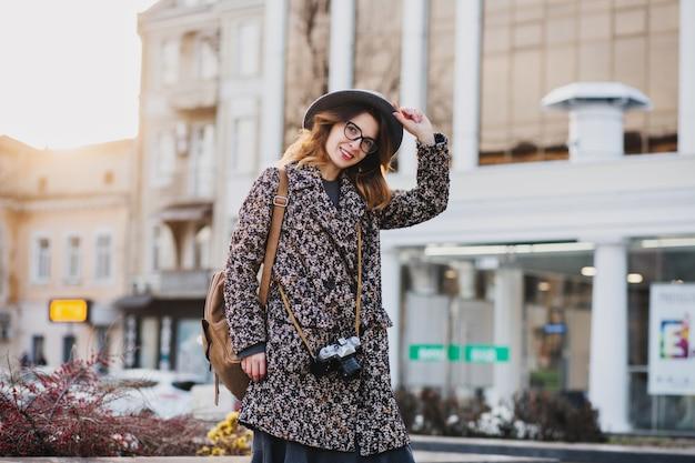 Openluchtportret van elegante jonge dame met bruine rugzak die jas en hoed draagt. aantrekkelijke vrouw met krullend haar spreken aan de telefoon terwijl het drinken van koffie op straat