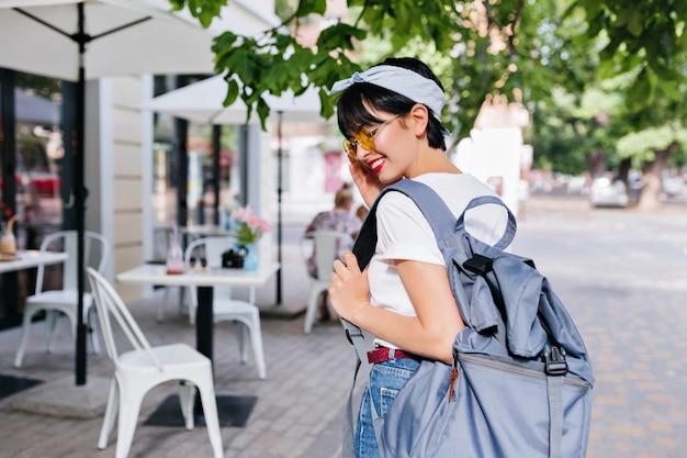 Openluchtportret van elegante vrouwelijke reiziger die in ochtend in openluchtrestaurant gaat lunchen