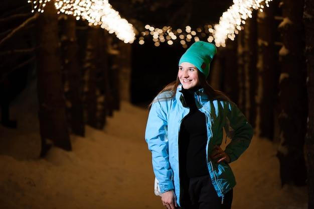 Openluchtportret van gelukkig glimlachend meisje. model poseren in het nachtpark met kerstverlichting. wintervakantie concept.